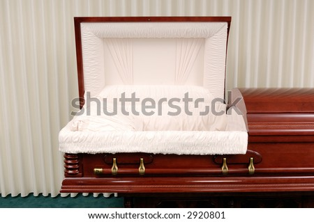 Wooden casket made of Cherry in a funeral home. - stock photo