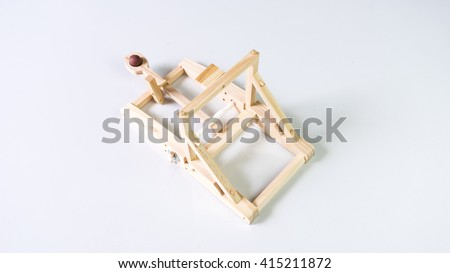 Wooden catapult isolated on empty white background. Concept of medieval weapon. Slightly de-focused and close-up shot. Copy space.