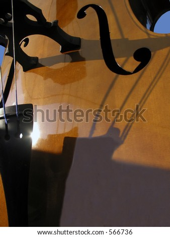 Wooden cello with shadows and blue sky