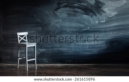 Wooden chair against a school desk for the letter, classroom - stock photo