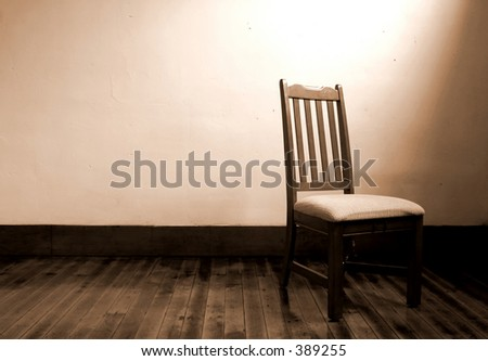 Wooden chair alone in a room lit by only a window. - stock photo
