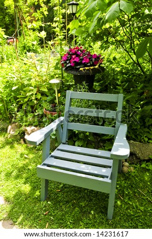Wooden chair in a secluded corner of lush green garden - stock photo