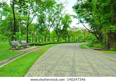 Wooden chair in beautiful park. - stock photo