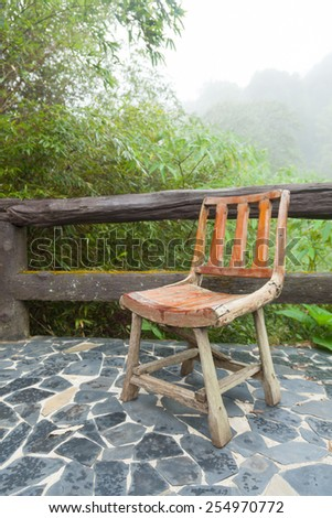Wooden chair on the balcony. Decking made of stone The outside terrace is a tree of moist air. - stock photo