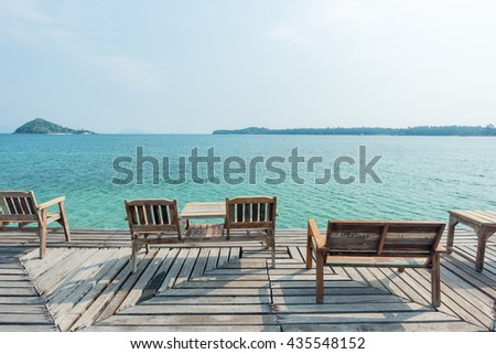 Wooden chair on wooden floor with beautiful ocean and blue sky scenery