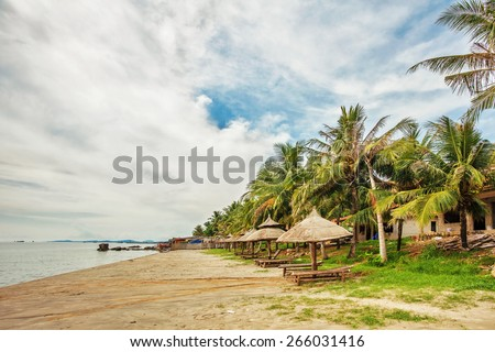 Wooden chairs and umbrellas near the old ruined hotel at Phu Quoc island in Vietnam - stock photo