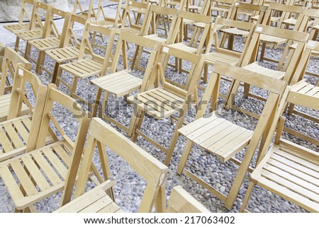 Wooden chairs in a concert, detail of one seat to see a show - stock photo