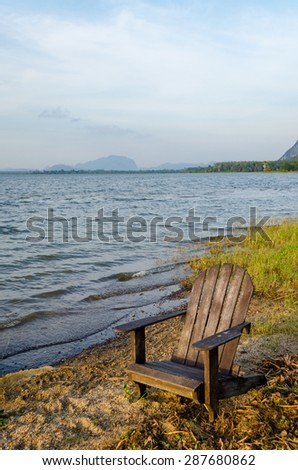 Wooden Chairs near lake.