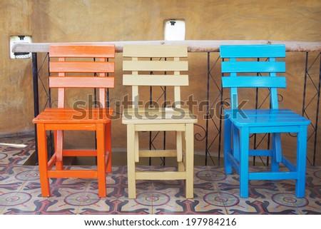 wooden chairs on ceramic tiles floor - stock photo