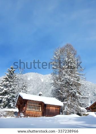 Wooden chalet cottage in winter, Swiss Alps, Switzerland                    - stock photo