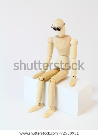 Wooden character with glasses staring, sitting in deep thought.