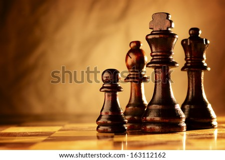 Wooden chess pieces standing in a line on a chessboard in dramatic sepia toned lighting with copyspace - stock photo