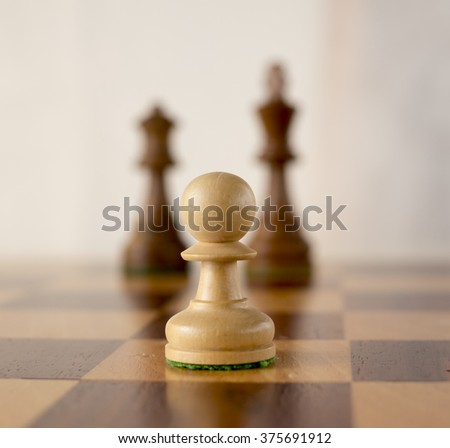wooden chess set, white pawn opposit enemy king and queen