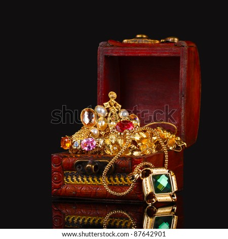 Wooden chest full of gold jewelry on black background - stock photo