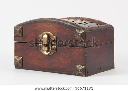 Wooden chest with metal lock and some carvings at the top.