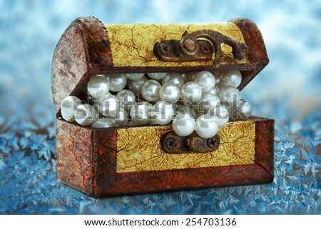 Wooden chest with white pearl necklace on frozen window - stock photo