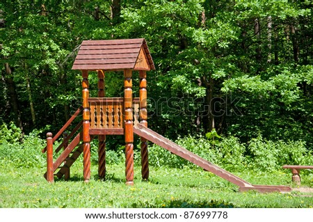 Wooden children's play set in a park in the summer