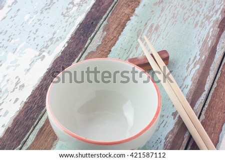 Wooden chopsticks and empty bowl on wooden background. - stock photo