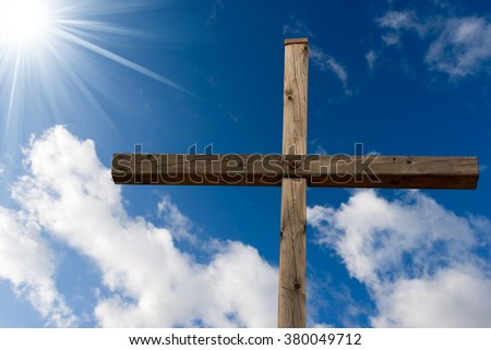 Wooden christian cross on blue sky with clouds and sun rays - stock photo