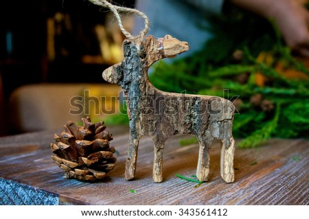 Wooden Christmas deer with pine cone on christmas background - stock photo