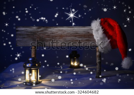 Wooden Christmas Sign And Santa Hat With Snow In Snowy Scenery. Copy Space Free Text For Advertisement. Blue Silent Night With Snowflakes And Sparkling Stars. Lantern And Candlelight - stock photo