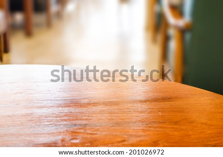 wooden circle table top and blur cafe background - stock photo