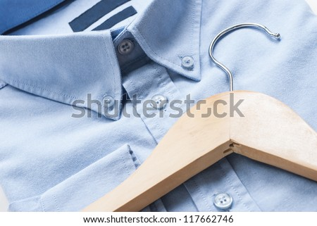 Wooden cloth hanger on top of blue shirt - stock photo