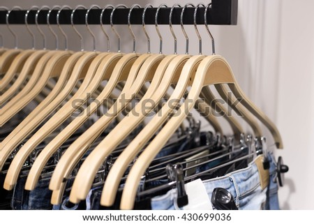 Wooden clothes hang on a shelf in a clothes store - stock photo