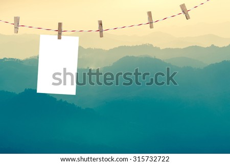 wooden clothes pin holding white sheets of photo paper over the landscape. (paper side 3x2) - stock photo