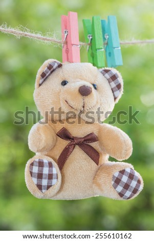 wooden clothespin hanging with teddy bear on rope, depth of field - stock photo