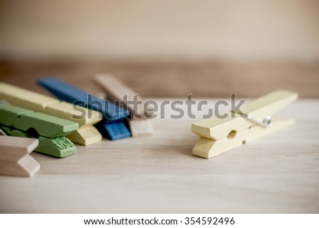 Wooden Clothespin on wood background. The concept of leadership. - stock photo