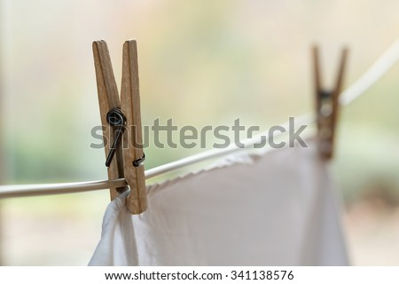 Wooden clothespins holding a white shirt on an outdoor laundry line.  - stock photo