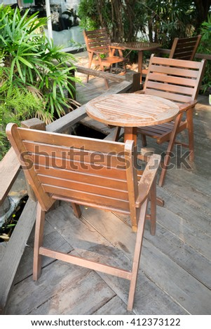 Wooden coffee table sets in an outdoor wood balcony next to green garden - bright lighting