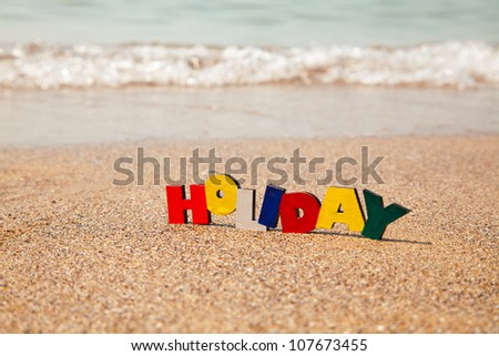 Wooden colorful word 'Holiday' on the sand