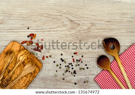 Wooden cooking spoon an checkered napkin on a board - stock photo