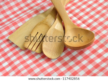 Wooden cooking utensils on plaid cloth - stock photo