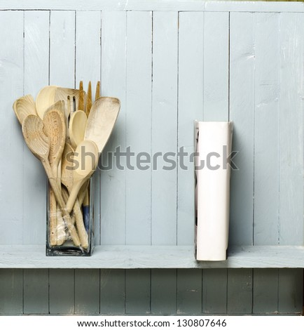 Wooden cooking utensils on shelf; good copy-space; photographed against rustic wall; add your own text to the blank spine of the 'cookery book' - stock photo