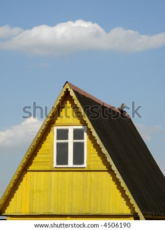 wooden cottage fragment against blue sky with clouds