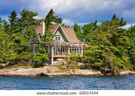 wooden cottage on the lake - stock photo