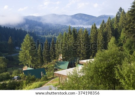 Wooden cottages on mountain hillside in Bieszczady Mountains, Poland - stock photo
