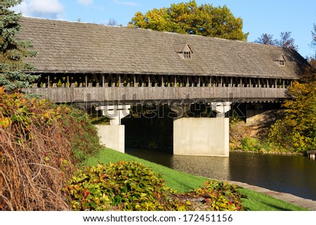 Wooden covered bridge, also known as Zehnders Holz Brucke, spans the Cass River in Frankenmuth Michigan. Warm autumn colors surround the wooden bridge. - stock photo