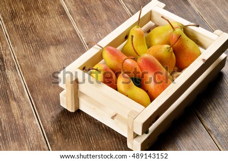 Wooden crate with organic pears on the table
