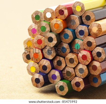 wooden crayon stack on wooden surface, extreme closeup - stock photo