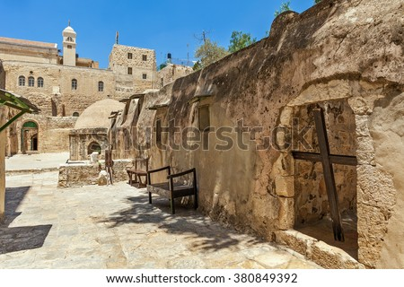 Wooden cross and stone monastic cells on roof of Church of the Holy Sepulcher in Jerusalem, israel. - stock photo