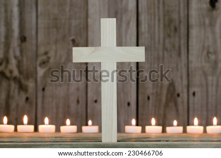 Wooden cross by row of burning candles with rustic wood background - stock photo