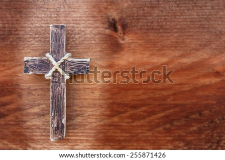 Wooden cross on old rustic wood background. The spotlight is on the holy cross - stock photo
