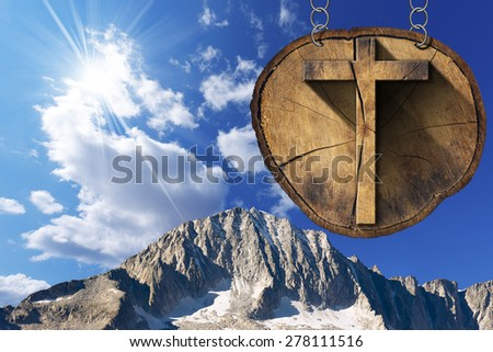 Wooden Cross on Tree Trunk - Italian Alps / Wooden Christian cross on a section of tree trunk, hanging from a metal chain. In the background the peaks of the Italian Alps - stock photo
