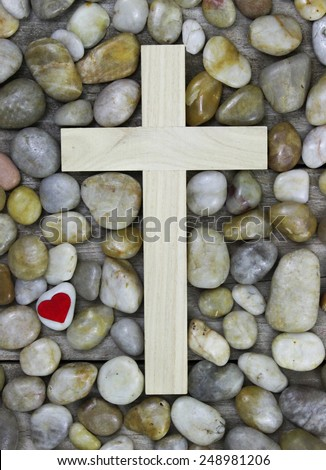 Wooden cross surrounded by stone background with red heart - stock photo