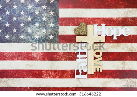 Wooden cross with Hope, Faith, Love and rope heart on vintage American flag canvas background - stock photo