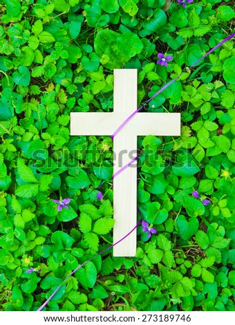 Wooden cross wrapped in purple ribbon with purple flower and green clover background - stock photo
